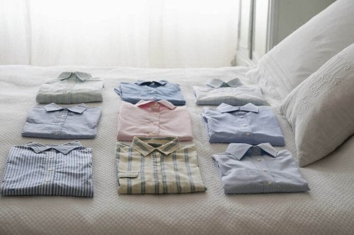 Folded shirts on a bed.