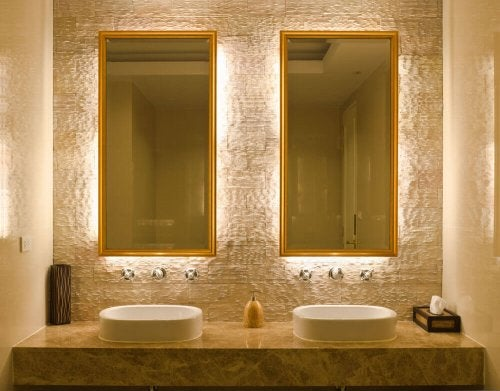 A gold bathroom with double mirrors.