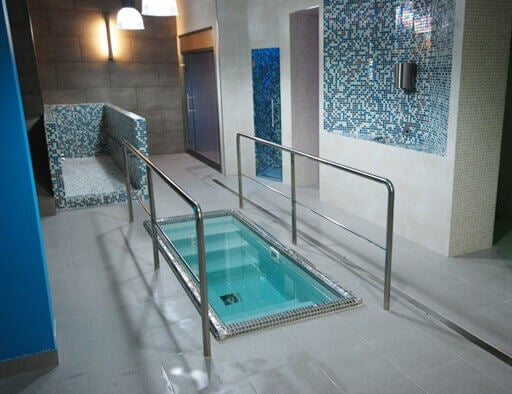 An indoor immersion pool with railing