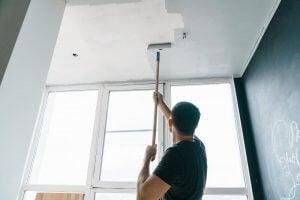 A man paints his ceiling.