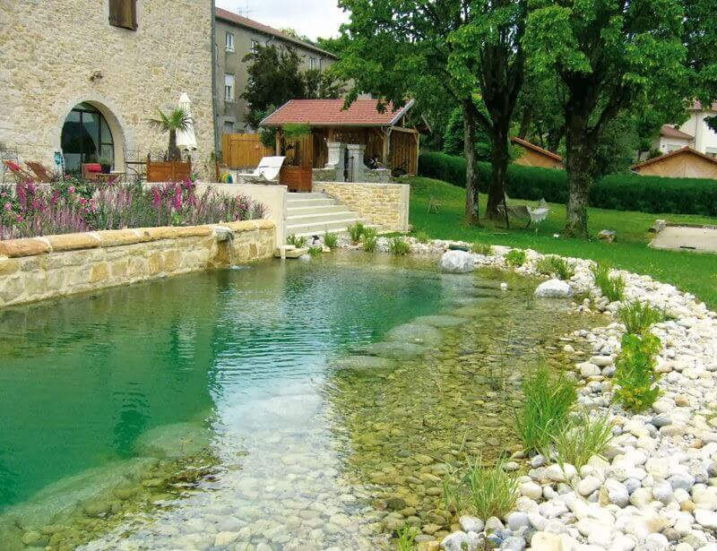A natural swimming pool with pebbles and plants on the border