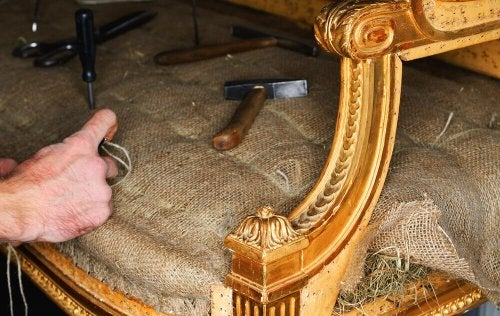 A person repairing a sofa.