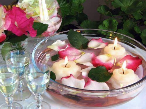 A rose petal and candle centerpiece.