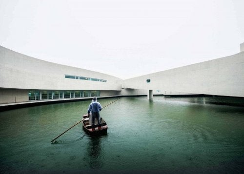 A man standing in a rowboat in water between wings of a building