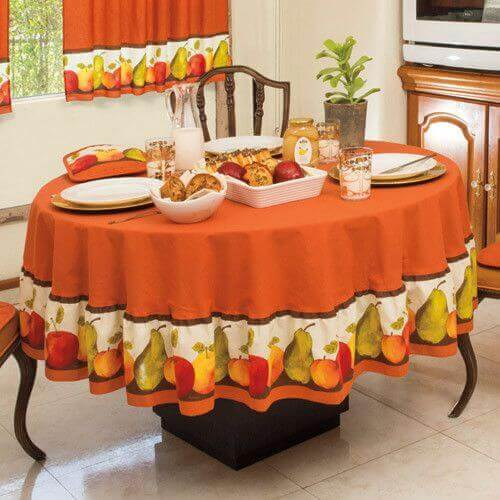 Table set with a festive tablecloth with a fruit design