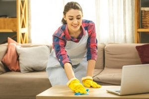 A woman cleaning a table.