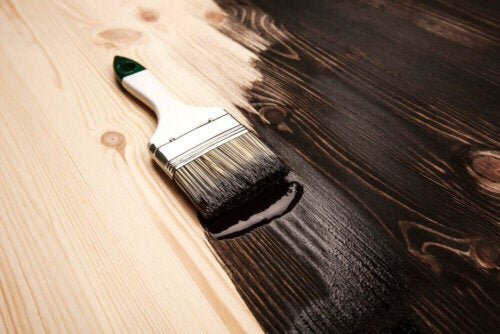 A brush with brown paint on top of a wooden surface.