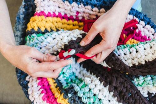 A person knitting a trapillo rug.