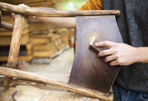 A person sanding a chair.