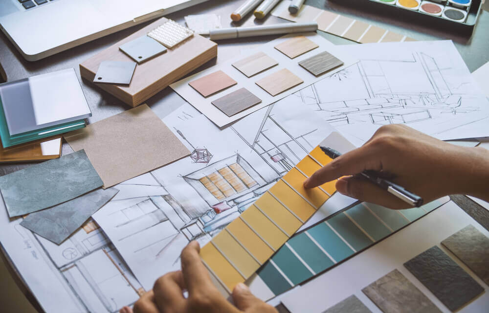 An architect works on a blueprint for house renovations.