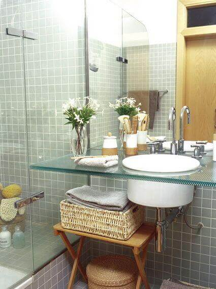 A bathroom with a glass countertop.