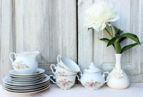 A tea set and a flower in a vase on a table.
