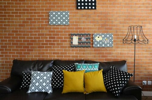 Room with a brick wall with black and other colors on the sofa