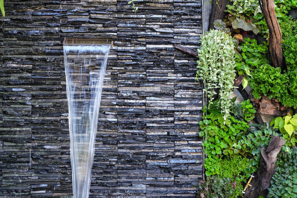 A spa fountain with water emerging from a wall.