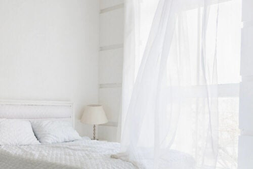 An all-white bedroom, one of the ten out-of-style decor trends.