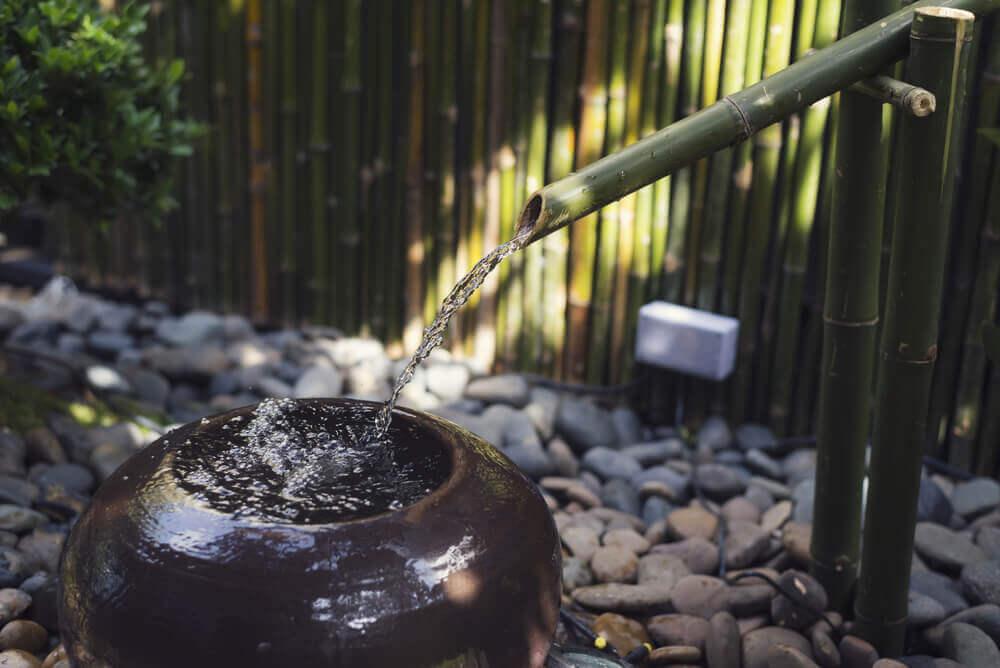 A zen fountain in a garden.