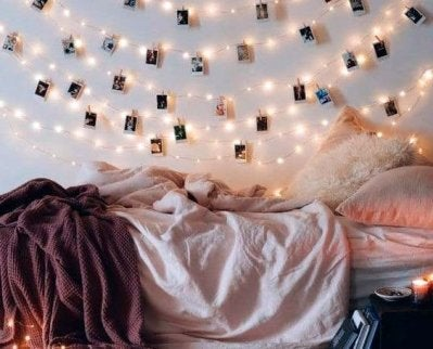 Using instant pictures with fairy lights on the wall to create a cozy environment