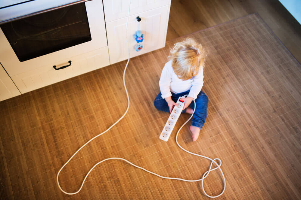 A child playing with a power strip.