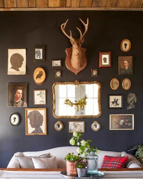 A collage of mirrors, portraits, deer heads and other elements of hunting home decor