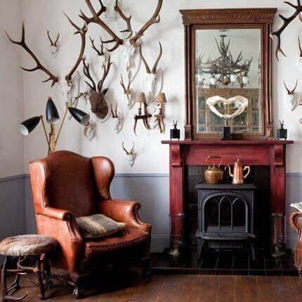 A living room decorated with several pieces of hunting home decor such as antlers and earthy tones
