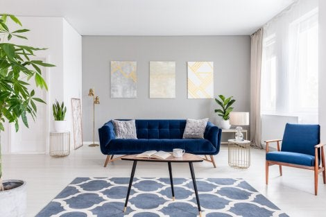 Navy blue sofa as the focal point of a white and gray living room