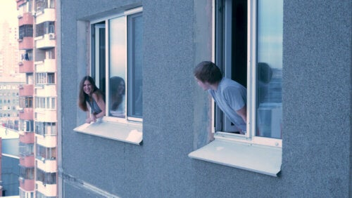Two neighbors talking to each other through windows.