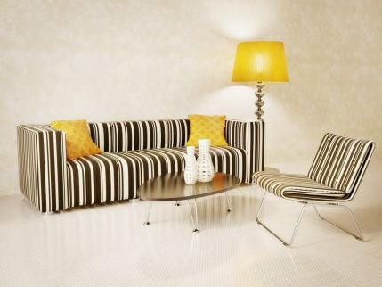 A striped black and white sofa with yellow accents is the perfect contrast in a plain room