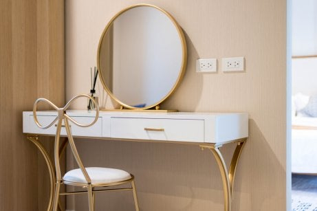 White and gold minimalist vanity with a matchin chair and mirror