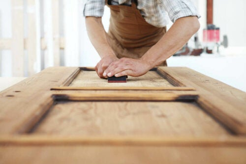 A man who is sanding a piece of furniture