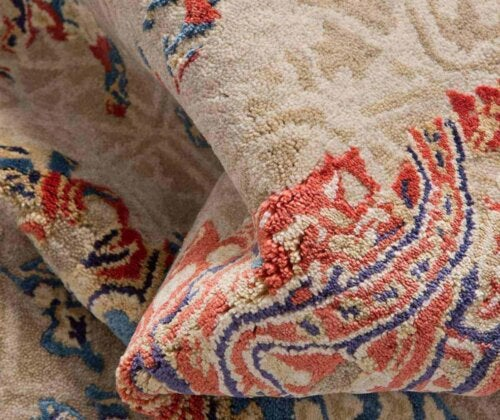 A tan rug with an orange and blue design.