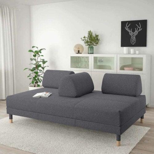 A gray sofa with a detachable back.