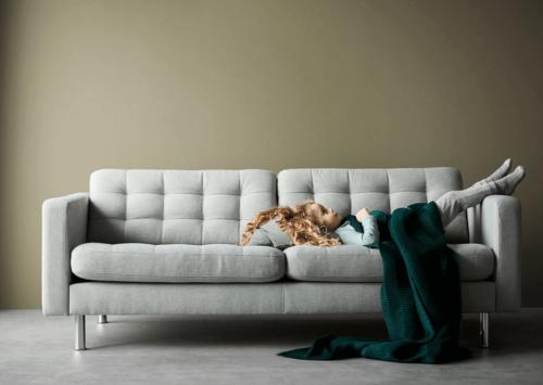 A little girl lying down on a gray sofa.