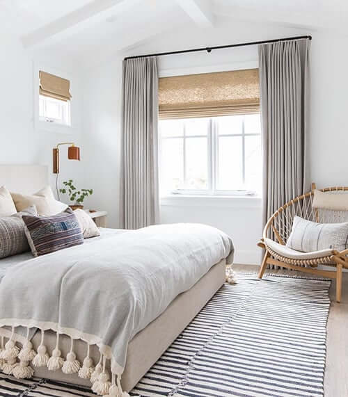 A mix of drapes and blinds in the bedroom.