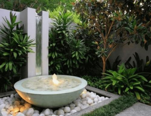 A round minimalist fountain in a garden.