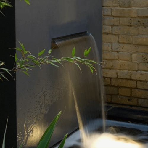 A waterfall fountain coming out of a wall.