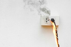 A faulty wall socket on fire.