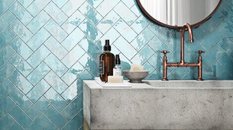 a bathroom with blue tiles on the wall with cool colors
