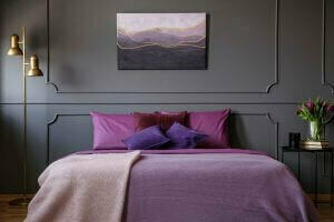 A bed with violet sheets and gray wall