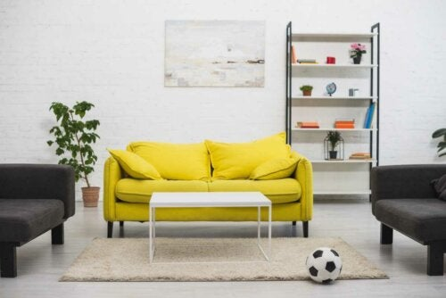 a living room with a bright yellow sofa and white walls in a second home