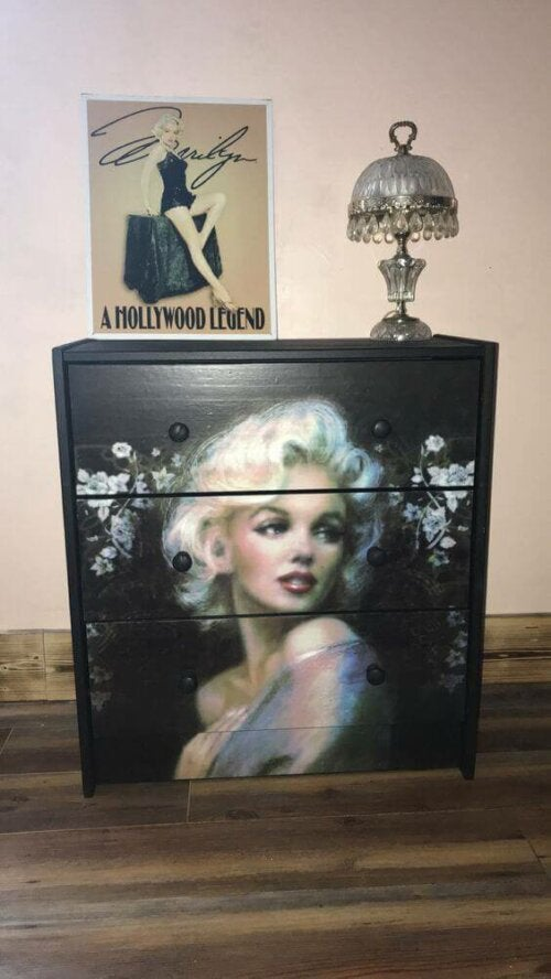 A dresser and a painting of some celebrities.
