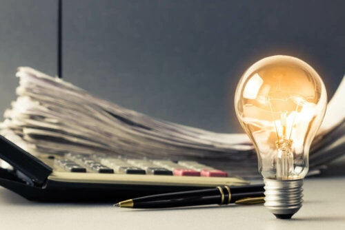A lightbulb magically lit-up beside some papers.