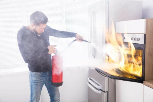A man putting out a fire hoping he has homeowners insurance.