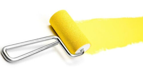 A paint roller with yellow paint.