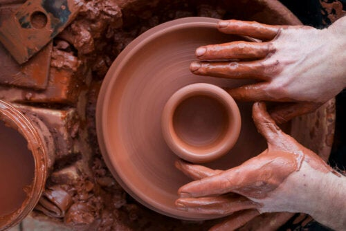 A person making their own pottery for a low-cost chic decor.
