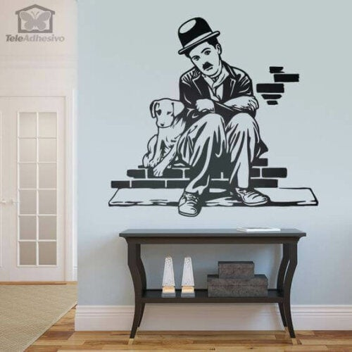 A print of Charlie Chaplin and his dog on a wall.