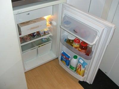 A small refrigerator in a corner.