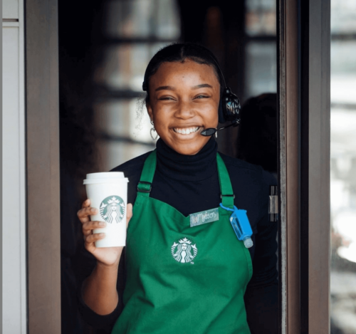 A smiling barista holding a customer's drink.