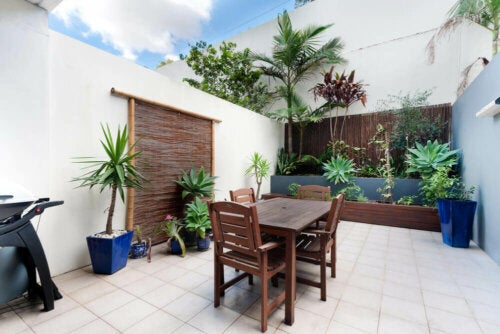 A tiled patio with a touch of green.