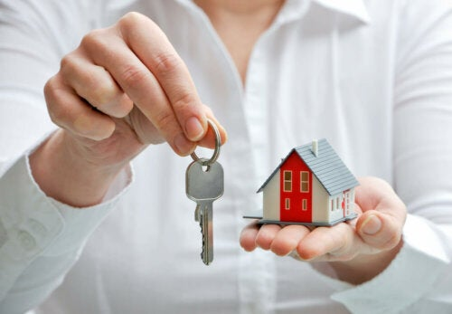 An agent gifting the keys to a house and holding a small plastic house.