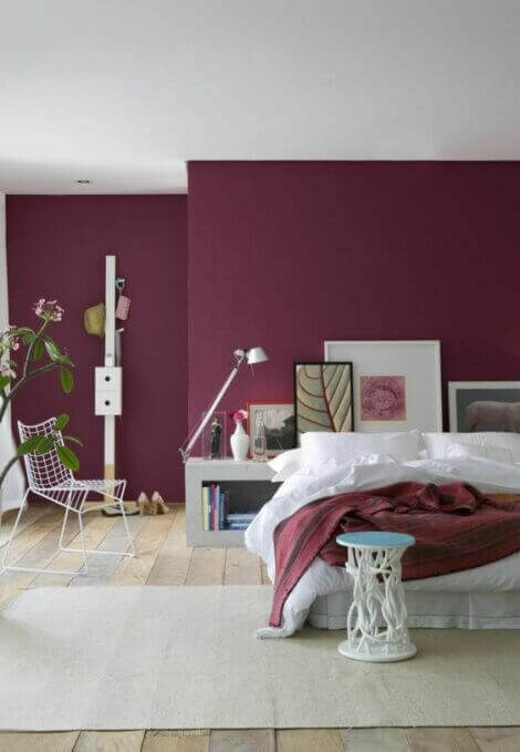 Bedroom with wine colored walls combined with white decor.